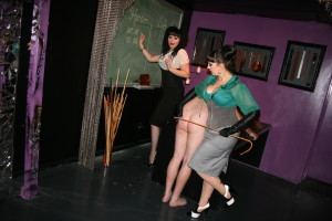 Mistress Electra Amore & Mistress Gabrielle correcting the ways of a wayward lad in The Fetish Palace school room in Adelaide.